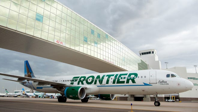 A Frontier Airbus A321 passes under the landmark pedestrian bridge at  Denver International Airport on May 7, 2017.