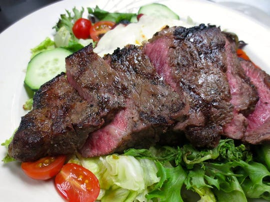 An 8-ounce New York strip steak tops a salad dressed with homemade basil balsamic at Neil Michael's Steakhouse in Atlantic Highlands.
