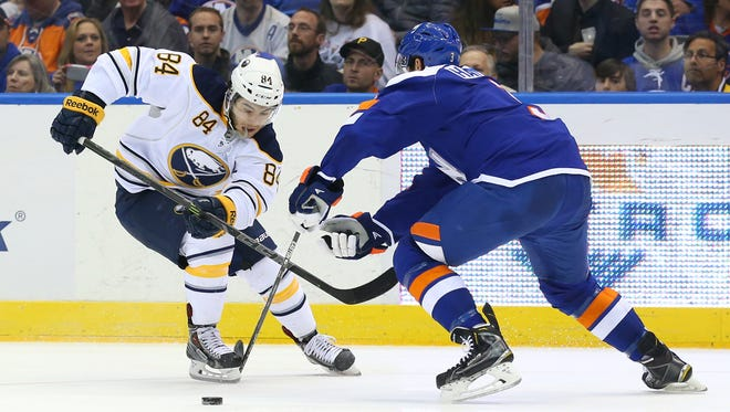 Buffalo Sabres center Phil Varone (84) is challenged by New York Islanders defenseman Travis Hamonic (3) during the second period at Nassau Veterans Memorial Coliseum in Uniondale, N.Y., on April 4, 2015.