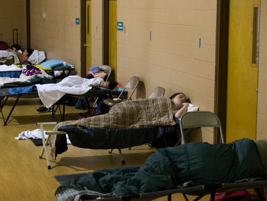 Women sleep on cots and the floor in a gym at Pathways