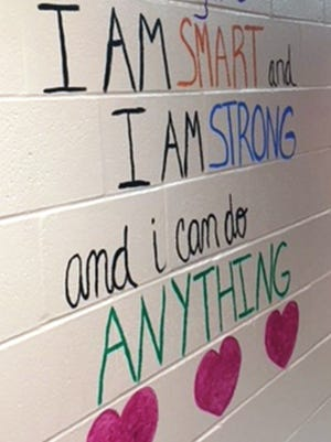Loveland Intermediate School teachers painted inspirational messages on the bathroom walls to promote a positive self-image to female students.