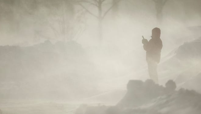 A woman walking around Lake Harriet in Minneapolis, Minn. paused at W. Minnehaha Parkway to shoot some video of the blowing snow with her cell phone.