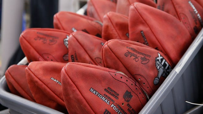 Official game balls for the NFL football Super Bowl XLIX sit in a bin before being laced and inflated at the Wilson Sporting Goods Co. in Ada, Ohio, Tuesday, Jan. 20, 2015. The New England Patriots will play the Seattle Seahawks in the Super Bowl on Feb. 1 in Glendale, Arizona.