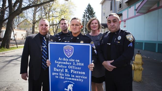 From left, retired Greece police officer Mike Boehm, Rochester police officer Steve Kovacic, Rochester Sgt. Justin Collins, Kristen Ferguson, the wife of Rochester police officer Russell Ferguson, and Irondequoit police officer Bill Rosica with the Badge of Honor Association hold a sign that will be unveiled at the corner of Hudson Avenue and Ernst Street, where Officer Daryl Pierson was killed in September.
