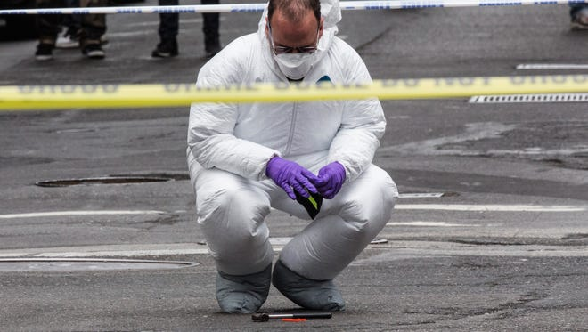 A crime scene investigator inspects a hammer used in an attack on a police officer on May 13 in New York City.