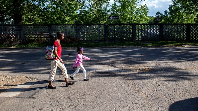 Maddison Rogers, 6, walks with mom Cicely Rogers to their apartment from the Children First/Communities in Schools after school program at Pisgah View Apartments in West Asheville, Wednesday.