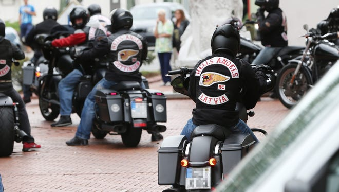 Members of the Hells Angels motorcycle gang wear gear with the club's logo.