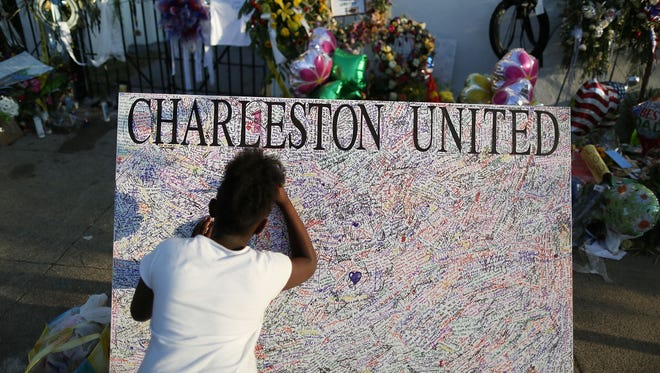 Jennice Barr, 10, leaves a message on a board set up in front of the Emanuel African Methodist Episcopal Church in Charleston, S.C.