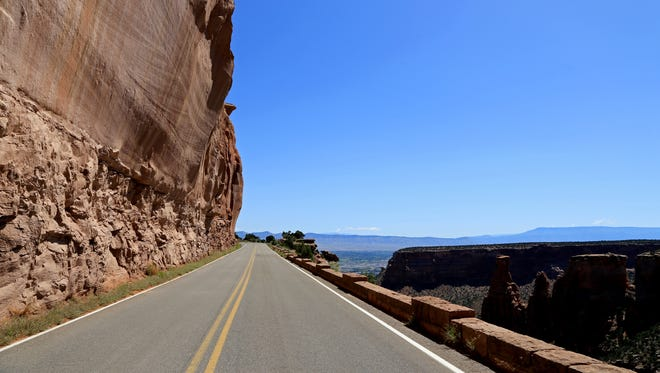 Rim Rock Drive often straddles the edge of the cliff as it winds around the rim above a series of canyons in Colorado National Monument.
