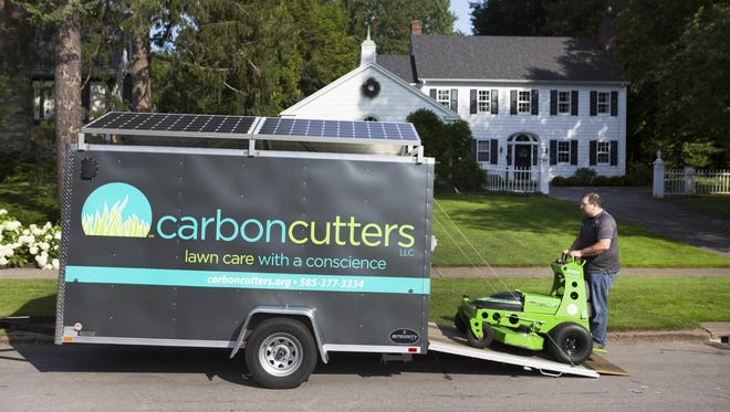 Steve Popp loads his electric mower into a trailer topped with solar panels after mowing a lawn in Brighton on Friday, July 10, 2015.