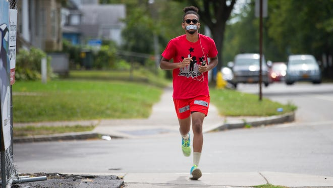 Micah Kalani Johnson, 23, runs down Genesee St. on Thursday, September 10, 2015. Johnson started running four miles everyday in honor of the victims of the shooting at the Boys and Girls Club last month. He plans to run to New York City next month.