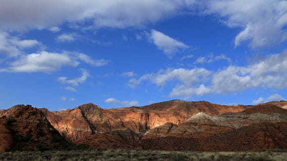 Patches of light shine through the clouds above Snow Canyon State Park as seen from the Butterfly Trail.