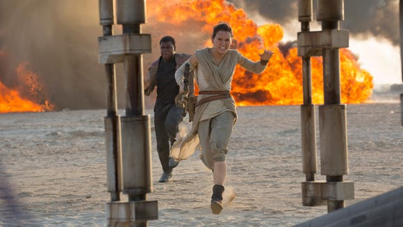 Finn (John Boyega) and Rey (Daisy Ridley) run for their