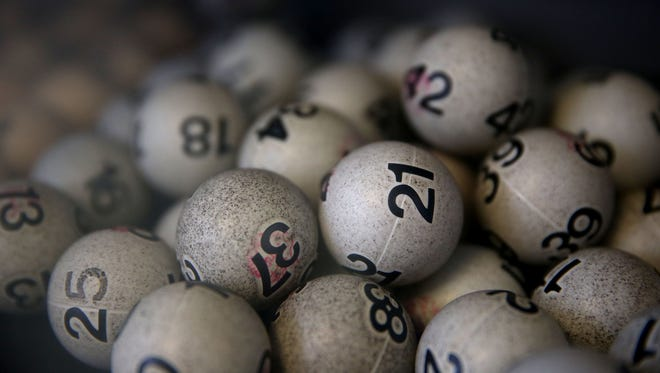 Old lottery balls are seen in a box Jan. 12, 2015, at Kavanagh Liquors in San Lorenzo, Calif., where customers have been lining up to buy Powerball tickets.