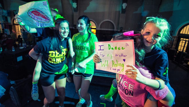 Children hold up signs while on the shoulders of UI students during the UI Dance Marathon at the Iowa Memorial Union main ballroom in Iowa City on Saturday, Febraury 7, 2015. The annual fundraiser has raised millions for the U of Iowa Childrens Hosptial.