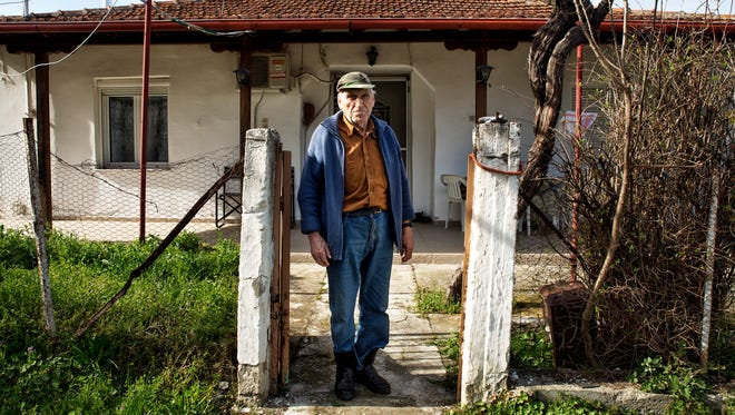 Antonis Zois, an 85-year-old Idomeni native, stands outside his home, from where he can see the refugee tents.
