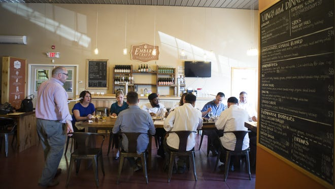 A group enjoys a meal in the taproom of Embark Craft Ciderworks at Lagoner Farms in Williamson in August 2015.