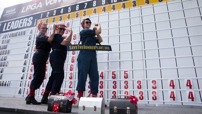 Volunteers dressed as Rosie the Riveter work the scoreboard during the third round of the Volvik Championship on Saturday in Ann Arbor.