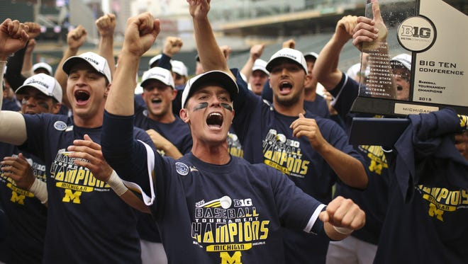 Michigan players sing their school's fight song after receiving the Big Ten championship trophy on Sunday, May 24, 2015, at Target Field in Minneapolis.