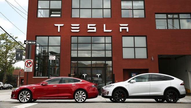 Tesla vehicles sit parked outside of a new Tesla showroom and service center in Red Hook, Brooklyn on July 5, 2016 in New York City.