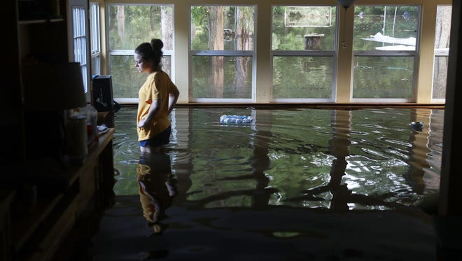 Leslie Andermann Gallagher surveys the flood damage to her home on Aug. 17, 2016, in Sorrento, La.  Last week Louisiana was overwhelmed with flood water causing at least twelve deaths and thousands of homes damaged by the floodwaters.