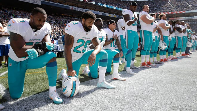 From left, Miami Dolphins' Jelani Jenkins, Arian Foster, Michael Thomas, and Kenny Stills, kneel during the singing of the national anthem before an NFL football game against the Seattle Seahawks, Sunday, Sept. 11, 2016, in Seattle.