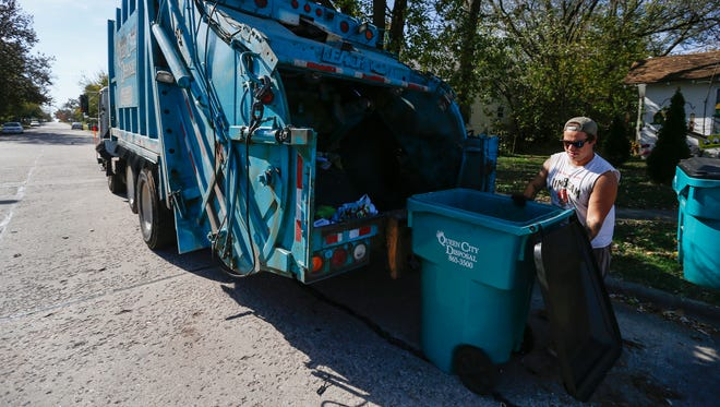 Thomas Nault, of Queen City Disposal, picks up trash on Prospect Avenue on Wednesday, November 2, 2016.