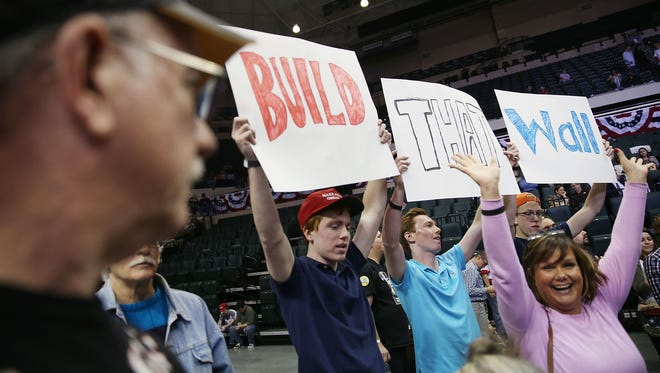 "People held signs proclaiming ""Build that wall"" as they waited for the start of a campaign rally for Donald Trump on Feb. 12, 2016, in Tampa, Fla."
