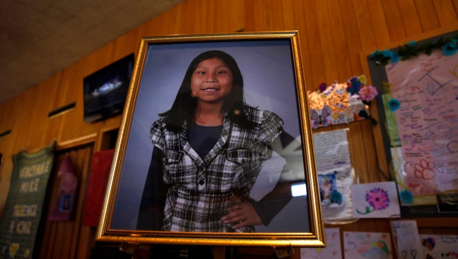 In this May 6, 2016 photo a portrait of Ashlynne Mike is on display inside the lobby of the Farmington Civic Center in Farmington, N.M. Mike's father has sued the tribe for failing to have an emergency notification system that he claims would have saved his daughter's life.