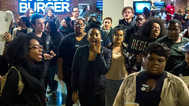 TaQueria Barrett, 23, of Chicago, leads a chant during a protest at the Eastern Michigan University Student Center on Tuesday, January 24, 2017 in Ypsilanti. The protestors gathered in response to recent punishment for another recent sit-in protest of the EMU student center.