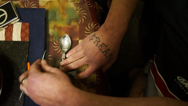 A heroin addict prepares to shoot up Suboxone, a maintenance drug for opioid dependence that is also highly addictive.