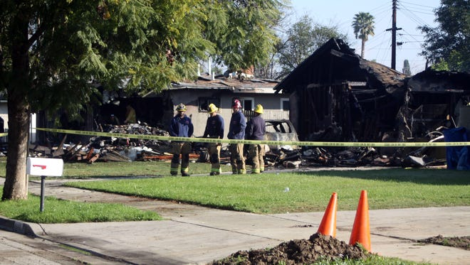 Firefighters stand Feb. 28, 2017, outside a Riverside, Calif., home that was destroyed when a small airplane hit it. Three passengers were killed in the crash and two others were injured.