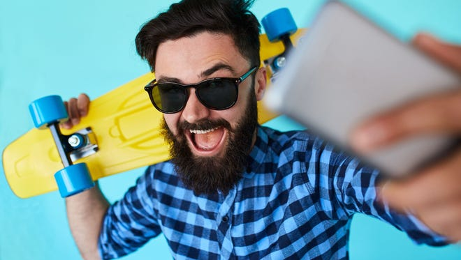 Young hipster with beard in glasses taking selfie and smiling.