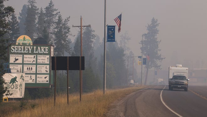 In this photo provided by the U.S. Forest Service, a pickup truck pulls a camper through the wildfire smoke in Seeley Lake in Missoula County, Mont., on Thursday, Aug. 10, 2017. Health officials in western Montana are strongly recommending residents of Seeley Lake leave town due to hazardous smoke from area wildfires.