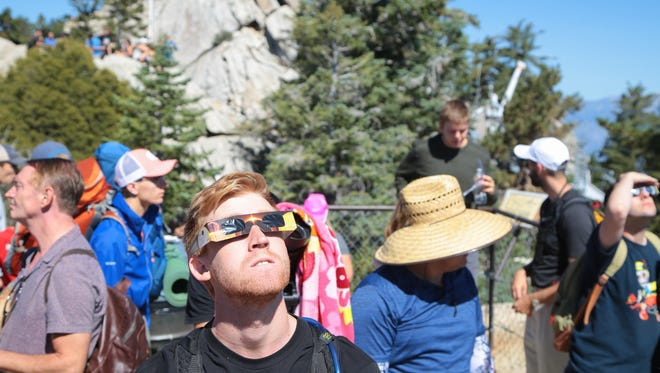 Visitors watch the eclipse from an upper deck of the Palm Springs Tramway Mountain Station, Monday, August 21, 2017. .