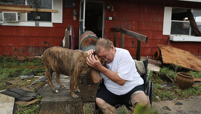 """Steve Culver cries with his dog Otis as he talks about what he said was the """"most terrifying event in his life,"""" when Hurricane Harvey blew in and destroyed most of his home while he and his wife took shelter in Rockport, Texas."""