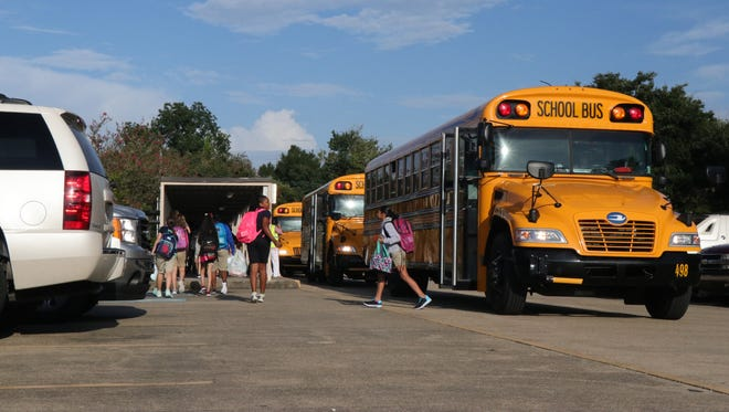 Students get off the bus at L.J. Alleman Middle on Aug. 9, 2017. Several schools have been closed this week because of heavy rain.
