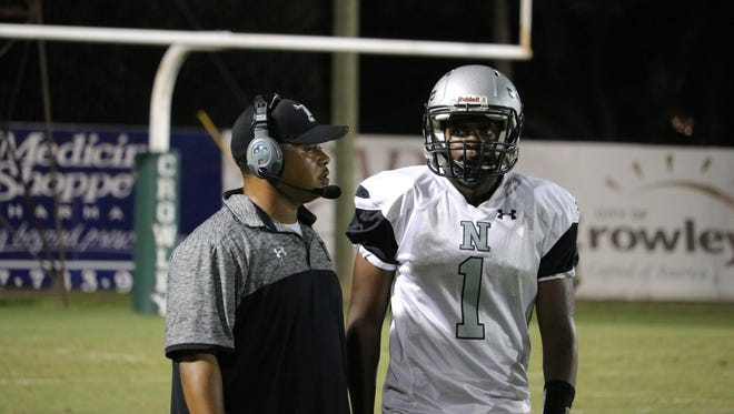 Northwest High coach Chris Edwards discusses strategy with his quarterback Montaz San (1) during the Raiders' game against the Crowley High Gents Friday Sept. 29, 2017.