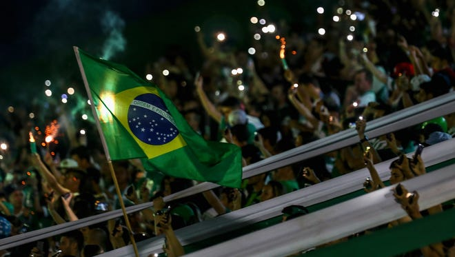 Fans pay tribute to the players of Brazilian team Chapecoense Real at the club's Arena Conda stadium on November 30, 2016 in Chapeco in the southern Brazilian state of Santa Catarina. The players were killed in a plane accident in the Colombian mountains. Players of the Chapecoense team were among the 77 people on board the doomed flight that crashed into mountains in northwestern Colombia.