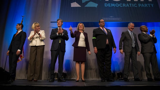 All seven Democratic candidates for governor, Nate Boulton, Cathy Glasson, Fred Hubbell, Andy McGuire, Jon Neiderbach, John Norris and Ross Wilburn take the stage during the Iowa Democratic Party's fall gala on Monday, Nov. 27, 2017, at Hy-Vee Hall in Des Moines.