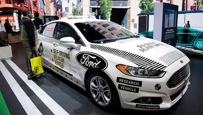 An attendee looks at Ford's self-driving delivery vehicle at CES International, Tuesday, Jan. 9, 2018, in Las Vegas.