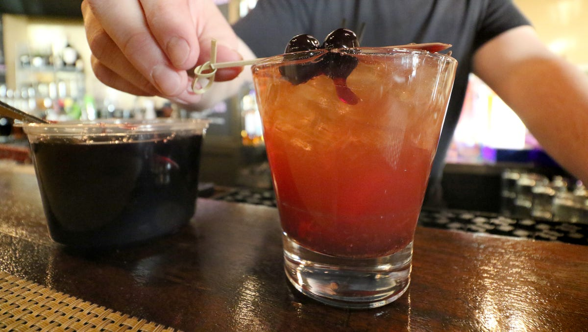 Bar Manager Adam Nobs adds a garnish of Louxardo marinated cherries to Pewaukee's Artisan 179 version of the classic Old Fashion that the call Ron and Mary's Brown Mumbler.