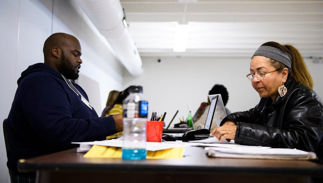 Maria Castrillon gets help with her taxes from Kenneth Bradley at the United Ministries-Learning Center on Friday, Feb. 2, 2018. The free tax assistance program is available to people who make less than $66 thousand a year.