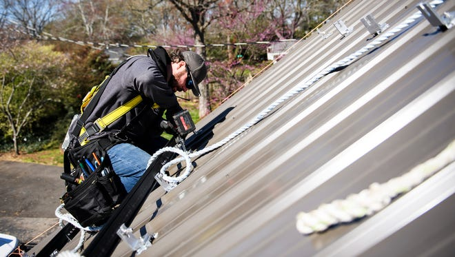 Nick Messer of Summit Builders LLC begins to install solar panels on a home on Thursday, March 15, 2018.