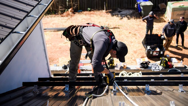 Ryan Phillips of Summit Solar begins to install solar panels on a home on Thursday, March 15, 2018.