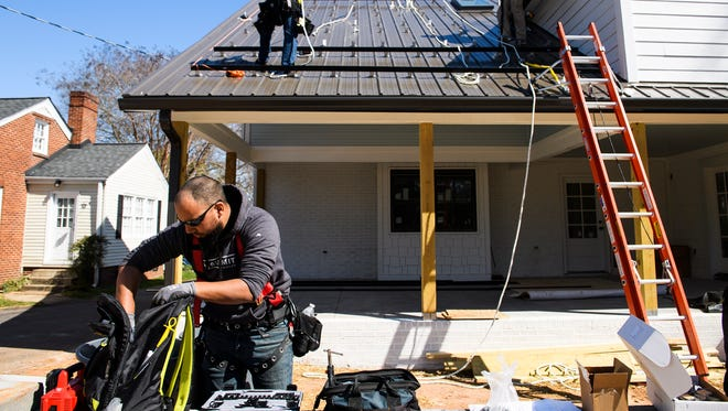 Jason Hernandez of Summit Builders LLC grabs tools as he and other works install solar panels on the roof of a home on Thursday, March 15, 2018.