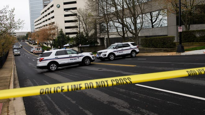 Greenville Police Department officials investigate the scene where a body was found outside of the Liberty Square parking garage in downtown Greenville on Monday, April 9, 2018.