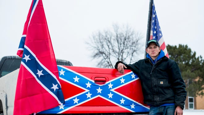"Cameron Meyers poses outside Bay City Western High School with his truck on Wednesday, April 18 2018, in Auburn, Mich. Meyers claims his Confederate flag was torn from his truck last Thursday, April 12, by a fellow Western student and his calls for the administration to discipline that student went unanswered. ""They shut me down,"" Myers said. ""They should be punished for destruction of property."" (Jacob Hamilton/The Bay City Times via AP)"