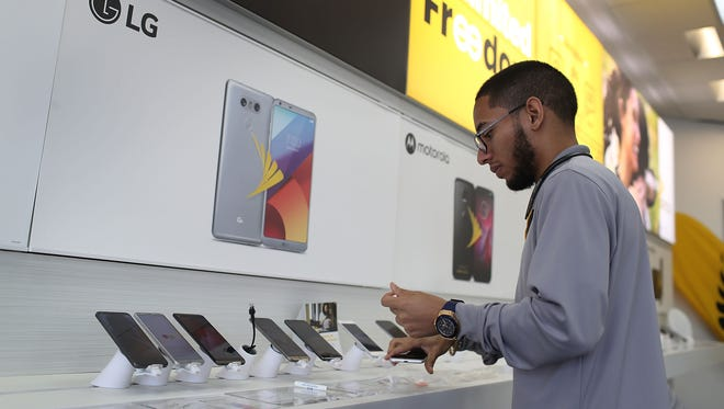 Jeffrey Quintana a sales rep at a Sprint store works on a cell phone display on Aug. 1, 2017 in Miami, Fla.