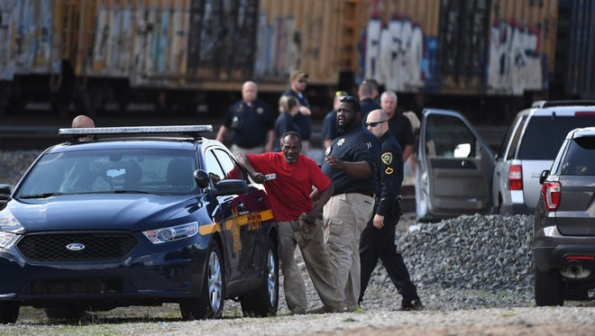 A man mourns near the scene where the body of a woman was found after she was struck by a cargo train near the Amtrak station in Greenville on Tuesday, May 8, 2018.